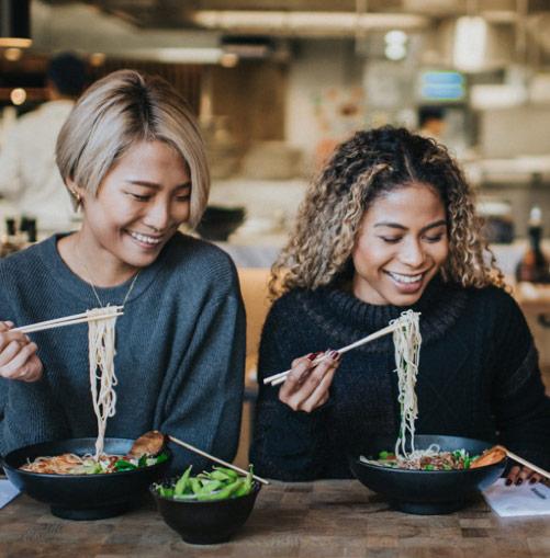 women enjoying wagamamas' ramen